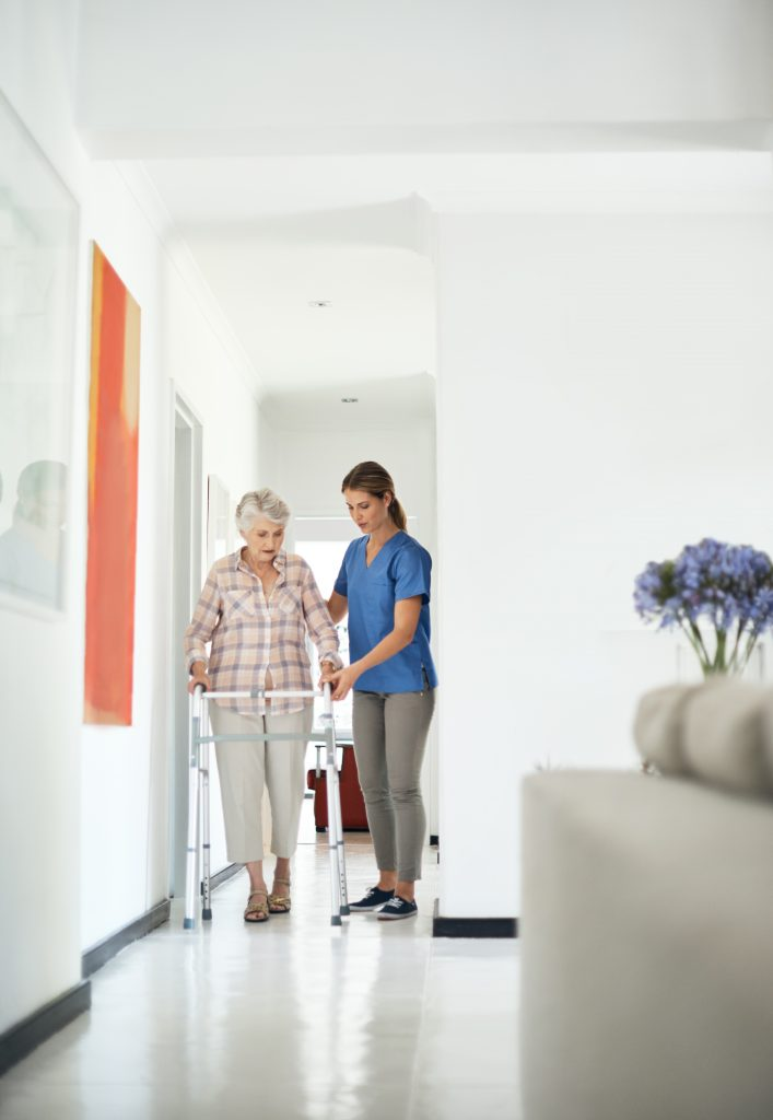 Shot of a friendly nurse helping her elderly patient to walk with a walker at home